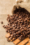 Coffee beans in a bag. Coffee beans in a burlap bag on a wooden background Royalty Free Stock Photography