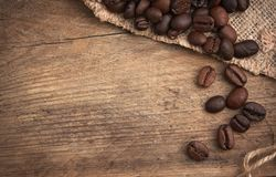 Coffee beans in a bag. On a wooden background royalty free stock photography