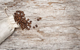 Coffee beans in a bag on the old wood Royalty Free Stock Image
