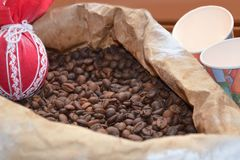 Coffee beans in the bag, paper cups and red decoration. royalty free stock image