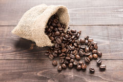 Coffee beans in a bag on wooden background Stock Images