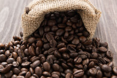 Coffee beans in a bag on wooden background Stock Photography