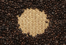 Coffee beans in bamboo and rattan background. Royalty Free Stock Images