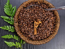 Coffee beans. A basket of Coffee beans with Cinnamon sticks on wooden background Stock Photo