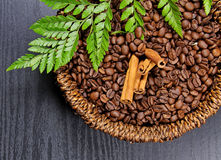 Coffee beans. A basket of Coffee beans with Cinnamon sticks on wooden background Stock Images