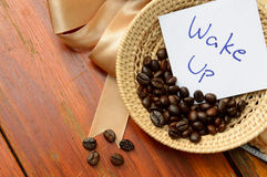 Coffee beans in basket and wake up note. On the wooden background Stock Photo