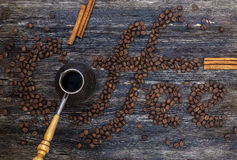 Coffee beans. Beautiful title Coffee written of coffee beans on wooden table Royalty Free Stock Image