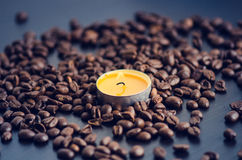 Coffee beans on a black background with candle. Raw coffee beans and fire from candle. Grained product. Hot drink Close up Royalty Free Stock Photography