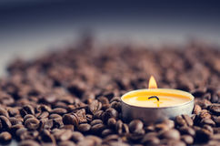 Coffee beans on a black background with candle. Raw coffee beans and fire from candle. Grained product. Hot drink Close up Stock Photo