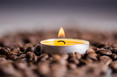 Coffee beans on a black background with candle. Raw coffee beans and fire from candle. Grained product. Hot drink Close up Stock Images