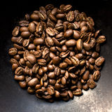 Coffee beans on black background. Fragrant fried coffee beans on a metal pan. Close up, top view Stock Image