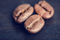 Coffee beans on a black background. Raw coffee beans. Grained product. Hot drink. Close up. Stock Image