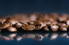 Coffee beans on a black background. Raw coffee beans. Grained product. Hot drink. Close up. Harvesting. Natural background. Energy. Reflection Stock Images