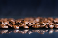 Coffee beans on a black background. Raw coffee beans. Grained product. Hot drink. Close up. Harvesting. Natural background. Energy. Reflection Stock Photos