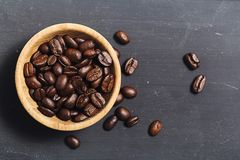 Coffee beans  on black board. Coffee beans in coconut shell bowl on black slate board background Stock Photos