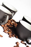 Coffee beans and black cups royalty free stock photo