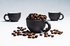 Coffee beans and black cups. Isolated on white stock photography