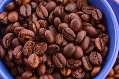 Coffee beans in blue cup isolated Stock Images