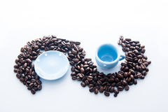 Coffee beans with blue espresso dishware Royalty Free Stock Images