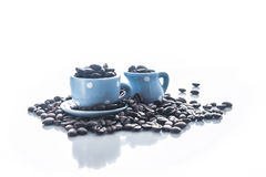 Coffee beans with blue espresso dishware Royalty Free Stock Photos