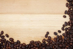 Coffee beans border on wooden desk Royalty Free Stock Photos