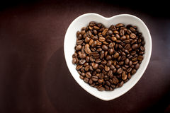 Coffee beans in a bowl in the form of heart Stock Image