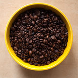 Coffee beans bowl. Freshly roasted coffee beans in bowl on brown table. Top view Stock Images