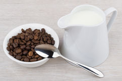 Coffee beans in bowl, teaspoon and milk jug Stock Images