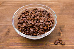 Coffee beans on the bowl on wood. Coffee beans on bowl on wooden table Stock Photos