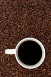 Coffee Beans and Brewed. Cup of coffee in a sea of coffee beans Royalty Free Stock Image