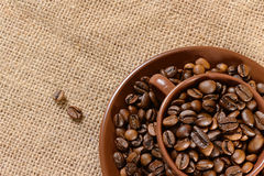Coffee beans in the brown cup. Fresh coffee beans in the brown cup which stands on the burlap Stock Photography