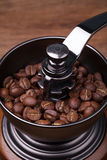 Coffee beans on the brown grinder wooden background Royalty Free Stock Photos