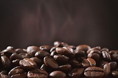 Coffee beans and brown wall with smoke. Closeup Stock Images