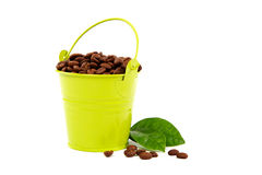 Coffee beans in a bucket and green leaves. Royalty Free Stock Images