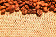 Coffee beans on burlap background Royalty Free Stock Images