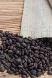 Coffee Beans and Burlap Bag. Coffee beans spilling out of a burlap bag on to a bamboo surface Royalty Free Stock Photos
