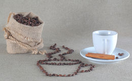 Coffee beans in burlap bag and cinnamon. Background Royalty Free Stock Photo