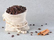Coffee beans in burlap bag and cinnamon. Background stock image