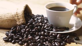 Coffee beans with burlap bag and coffee cup. Slow motion of coffee beans with burlap bag and hand taking a cup of coffee on the wooden table stock footage