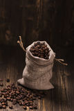 Coffee beans in burlap bags over wooden background. Vintage style. Selective focus Royalty Free Stock Image
