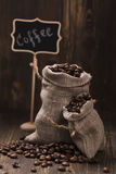 Coffee beans in burlap bags over wooden background. Vintage style. Selective focus Stock Images