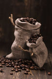 Coffee beans in burlap bags over wooden background. Vintage style. Selective focus Stock Photography
