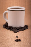 Coffee beans on burlap, with a coffee cup on background Royalty Free Stock Photos