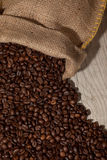 Coffee beans in burlap sack against dark wood Stock Photo