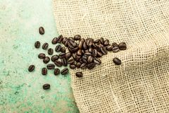 Coffee beans on a burlap sack and blue tiles. Delicious brown coffee beans, with a gunny bag on the floor. The blue and aqua tile creates tasteful imagery. Black Stock Photography