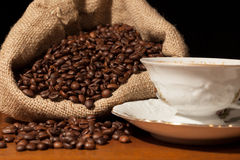Coffee beans in burlap sack , dark background Royalty Free Stock Images