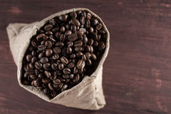 Coffee beans in burlap sack on wooden background Royalty Free Stock Image