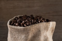 Coffee beans in burlap sack on wooden background Royalty Free Stock Photo