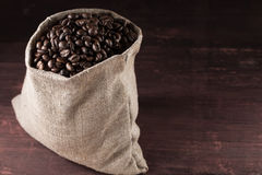Coffee beans in burlap sack on wooden background Royalty Free Stock Images