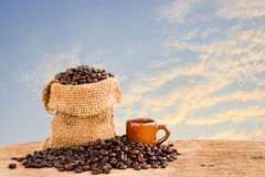 Coffee beans in burlap sack on wooden with blurred background Royalty Free Stock Photos